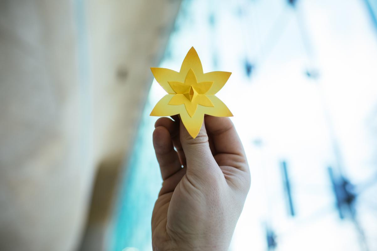 ludzka dłoń trzyma żółty papierowy żonkil, symbol akcji Żonkile